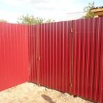 Красный забор на участке из профнастила